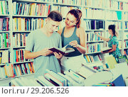 Купить «Teenagers reading book together and choosing literature», фото № 29206526, снято 16 сентября 2016 г. (c) Яков Филимонов / Фотобанк Лори