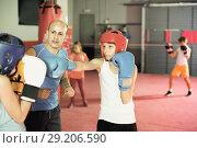 Купить «Two young boxer wearing gloves and helmet sparring», фото № 29206590, снято 12 апреля 2017 г. (c) Яков Филимонов / Фотобанк Лори