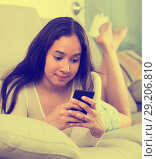 Купить «Young glad woman lying with mobile», фото № 29206810, снято 30 мая 2017 г. (c) Яков Филимонов / Фотобанк Лори