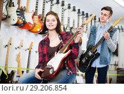 Pretty female and male teenagers customers examining electric guitars. Стоковое фото, фотограф Яков Филимонов / Фотобанк Лори