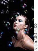 Купить «Beautiful young brunette woman with soap bubbles on black background», фото № 29214430, снято 14 августа 2018 г. (c) Serg Zastavkin / Фотобанк Лори