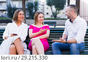 Купить «Young male is acquaintance with girls who are sitting on bench», фото № 29215330, снято 18 октября 2017 г. (c) Яков Филимонов / Фотобанк Лори