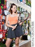Купить «Girl standing in t-shirt in sporting goods store with racket», фото № 29215566, снято 15 мая 2017 г. (c) Яков Филимонов / Фотобанк Лори