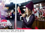 Купить «Woman choosing Christmas decoration at market», фото № 29215614, снято 22 декабря 2016 г. (c) Яков Филимонов / Фотобанк Лори
