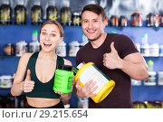 Купить «Young muscular people giving thumps up on background with shelves of sport nutrition products», фото № 29215654, снято 12 апреля 2018 г. (c) Яков Филимонов / Фотобанк Лори