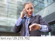 Businesswoman hurrying and watching on wristwatch. Стоковое фото, фотограф Яков Филимонов / Фотобанк Лори