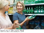 Купить «Mother with adult daughter selected the water in the shop», фото № 29223754, снято 15 октября 2018 г. (c) Татьяна Яцевич / Фотобанк Лори