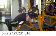 Bodybuilder performing incline barbell press exercise on a bench in the gym. Стоковое видео, видеограф Константин Шишкин / Фотобанк Лори