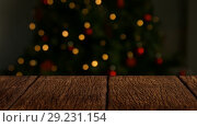 Купить «Wooden foreground with Christmas background of tree and lights», видеоролик № 29231154, снято 8 июля 2020 г. (c) Wavebreak Media / Фотобанк Лори