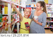 Купить «Woman with daughter are choosing fresh goods in food department», фото № 29231814, снято 5 июня 2017 г. (c) Яков Филимонов / Фотобанк Лори