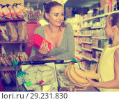 Купить «Woman with daughter are choosing fresh goods in food department», фото № 29231830, снято 5 июня 2017 г. (c) Яков Филимонов / Фотобанк Лори