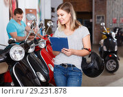 Купить «Smiling female is shopping and choosing new motobike in moto store.», фото № 29231878, снято 8 мая 2018 г. (c) Яков Филимонов / Фотобанк Лори