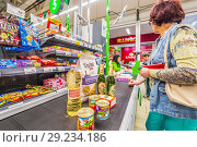 Купить «Russia, Samara, August, 2018: a woman with purchased products is at the cashier's desk in the supermarket. text in Russian: cat litter, pate», фото № 29234186, снято 20 августа 2018 г. (c) Акиньшин Владимир / Фотобанк Лори