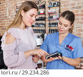 Купить «Woman client paying for services in nail salon», фото № 29234286, снято 30 мая 2018 г. (c) Яков Филимонов / Фотобанк Лори
