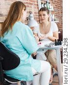 Купить «Woman polishing nails to unhappy female client in modern beauty salon», фото № 29234298, снято 30 мая 2018 г. (c) Яков Филимонов / Фотобанк Лори