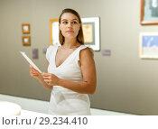 Купить «Woman observing museum exposition», фото № 29234410, снято 28 июля 2018 г. (c) Яков Филимонов / Фотобанк Лори