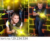 Купить «Excited young girl aiming laser gun at other players during lase», фото № 29234534, снято 3 сентября 2018 г. (c) Яков Филимонов / Фотобанк Лори
