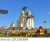 Купить «Children's playground on background of construction of St. Nicholas Church in new modern area of Pavshinsky floodplain», фото № 29234894, снято 11 октября 2018 г. (c) Валерия Попова / Фотобанк Лори