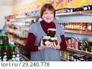 Купить «female purchaser choosing canned jar of jam», фото № 29240778, снято 15 декабря 2017 г. (c) Яков Филимонов / Фотобанк Лори