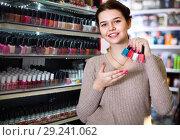 Купить «Smiling woman customer deciding on nail polish», фото № 29241062, снято 21 февраля 2017 г. (c) Яков Филимонов / Фотобанк Лори