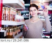Купить «young woman customer deciding on perfume variants in cosmetics shop», фото № 29241086, снято 21 февраля 2017 г. (c) Яков Филимонов / Фотобанк Лори