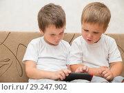 Купить «Two boys playing games on smartphone», фото № 29247902, снято 29 августа 2018 г. (c) Юлия Бабкина / Фотобанк Лори