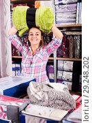 Купить «Girl customer looking for coverlet», фото № 29248202, снято 20 марта 2019 г. (c) Яков Филимонов / Фотобанк Лори