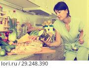 Купить «Portrait of adult woman who is checking conservation before cooking new recipe», фото № 29248390, снято 26 июня 2019 г. (c) Яков Филимонов / Фотобанк Лори