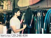 Купить «portrait of interested male surfer choosing suit for surfing in the store», фото № 29248434, снято 22 августа 2017 г. (c) Яков Филимонов / Фотобанк Лори
