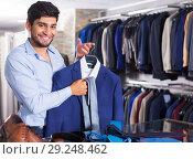Купить «Man demonstrating suit in shop», фото № 29248462, снято 20 июня 2017 г. (c) Яков Филимонов / Фотобанк Лори