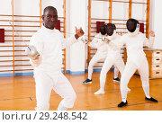 Купить «Sporty african american man fencer practicing effective fencing techniques», фото № 29248542, снято 11 июля 2018 г. (c) Яков Филимонов / Фотобанк Лори