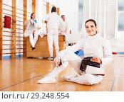Купить «Woman in uniform sitting on floor at fencing training», фото № 29248554, снято 11 июля 2018 г. (c) Яков Филимонов / Фотобанк Лори