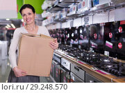 Купить «Female with packed purchases talking by phone in store», фото № 29248570, снято 21 февраля 2018 г. (c) Яков Филимонов / Фотобанк Лори