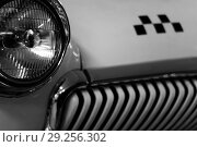 Monochrome fragment of the front part of a vintage taxi car, focus on the headlight, checker emblem and radiator in blur. Стоковое фото, фотограф Евгений Харитонов / Фотобанк Лори