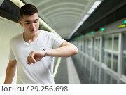 Купить «Man looking at watch on underground station», фото № 29256698, снято 24 августа 2018 г. (c) Яков Филимонов / Фотобанк Лори