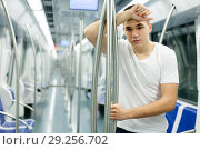 Купить «Tired man standing in underground carriage», фото № 29256702, снято 24 августа 2018 г. (c) Яков Филимонов / Фотобанк Лори