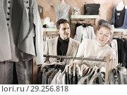Купить «Smiling woman and man are choosing variety clothes on hanger», фото № 29256818, снято 12 марта 2018 г. (c) Яков Филимонов / Фотобанк Лори