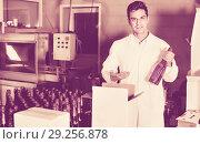Купить «Man standing in packing section on winemaking factory», фото № 29256878, снято 21 сентября 2016 г. (c) Яков Филимонов / Фотобанк Лори