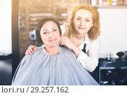 Купить «Woman is satisfied with work of adult haircutter», фото № 29257162, снято 7 марта 2017 г. (c) Яков Филимонов / Фотобанк Лори
