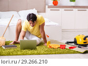 Купить «Young handsome man cleaning the bedroom and sitting at the compu», фото № 29266210, снято 28 июня 2018 г. (c) Elnur / Фотобанк Лори