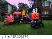Купить «The house is decorated for Halloween: Inflatable train with the dead, big pumpkin, ghost and black cat. Night, Houston, Texas, United States», фото № 29266870, снято 18 октября 2018 г. (c) Ирина Кожемякина / Фотобанк Лори