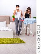 Купить «Young woman doing ironing for her husband», фото № 29272262, снято 27 июня 2018 г. (c) Elnur / Фотобанк Лори