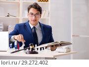 Купить «Young lawyer playing chess to train his court strategy and tacti», фото № 29272402, снято 31 июля 2018 г. (c) Elnur / Фотобанк Лори