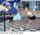 Купить «Couple stretching before workout at gym», фото № 29274302, снято 16 июля 2018 г. (c) Яков Филимонов / Фотобанк Лори