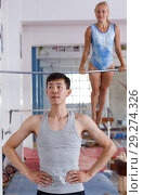 Купить «Man gymnast training gymnastic action at gym, woman on background», фото № 29274326, снято 18 июля 2018 г. (c) Яков Филимонов / Фотобанк Лори
