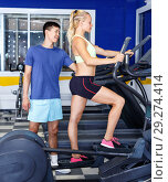 Young fitness man and woman doing cardio workout on fitness machines at gym. Стоковое фото, фотограф Яков Филимонов / Фотобанк Лори