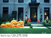 Купить «The house is decorated for Halloween:Many different pumpkins with faces and two dead man butlers with signs in their hands. Night, Houston, Texas, United States», фото № 29275558, снято 18 октября 2018 г. (c) Ирина Кожемякина / Фотобанк Лори