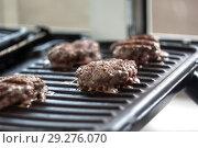 Купить «Meat - chicken cutlet to fry on an electric grill», фото № 29276070, снято 13 июля 2018 г. (c) Tetiana Chugunova / Фотобанк Лори