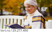 Купить «happy senior woman reading book at autumn park», видеоролик № 29277450, снято 22 октября 2018 г. (c) Syda Productions / Фотобанк Лори