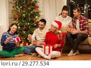 Купить «friends celebrating christmas and opening presents», фото № 29277534, снято 17 декабря 2017 г. (c) Syda Productions / Фотобанк Лори